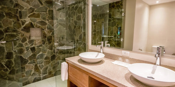 Generic bathroom with double ceramic sinks on and single-hole chrome faucets on granite counter tops. Glass and stone shower.